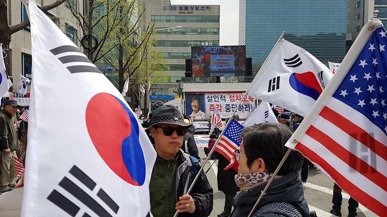 människor i gatubild med sydkoreanska flaggor i händerna i bakgrunden en bild på Park Geun-Hye, avsatte presidenten i Sydkorea