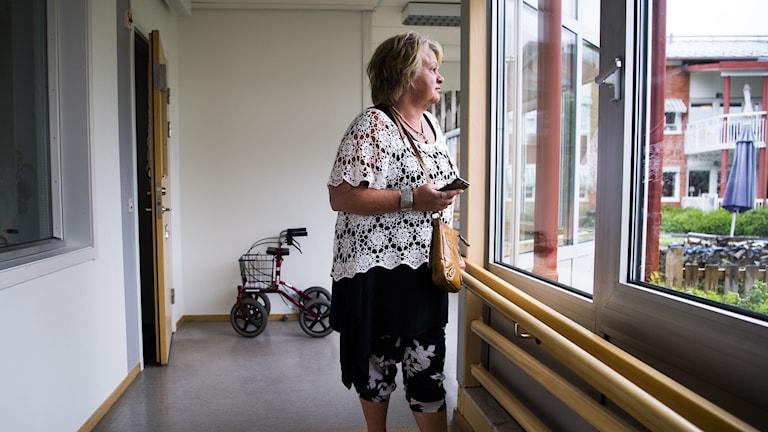 Kvinna tittar ut genom fönster i korridor på äldreboende.