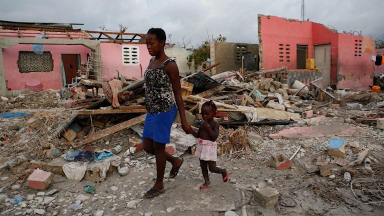 Invånare promenerar bland skadade byggnader och skräp i ett kustsamhälle som nästan helt förstördes av orkanen Matthew.