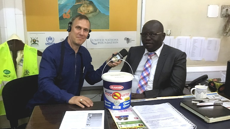 Globala hälsokorrespondenten Johan Bergendorff med Jimmy Opigo, som leder malariakampen vid Ugandas hälsodepartement. Här med den väggfärg som innehåller myggift som ett nytt vapen i kampen mot malaria.