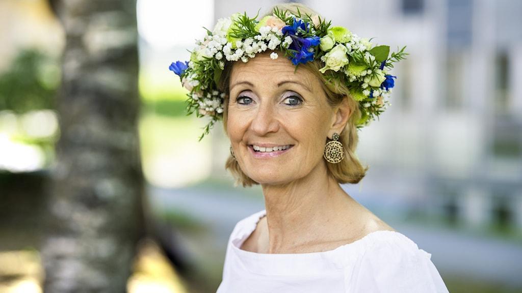 Bibi Rödöö på Sveriges Radio med en midsommakrans och en somrig björk i bakgrunden. Hon har i drygt 20 år jobbat med programmet Sommar i P1.