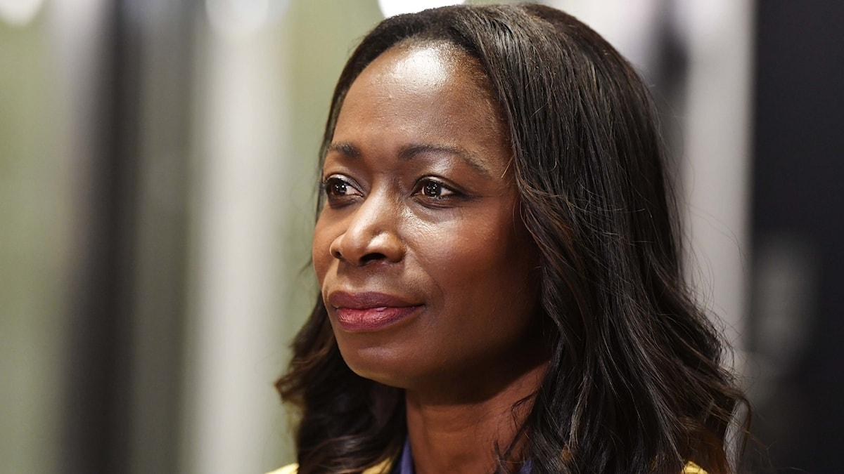 Kvinna med mörkt hår tittar åt sidan.