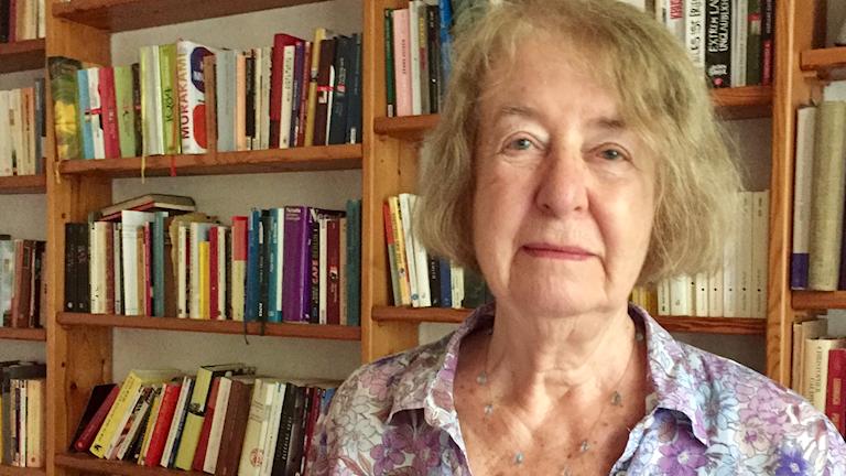 äldre kvinna tittar rakt in kameran, stående framför bokhyllor