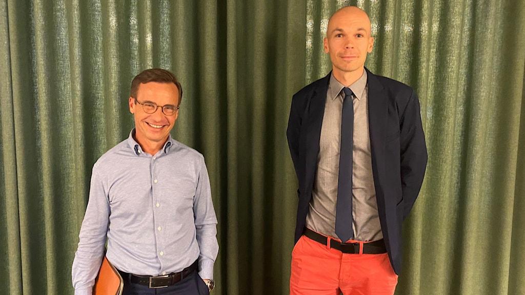 Två män står bredvid varandra framför en grön gardin