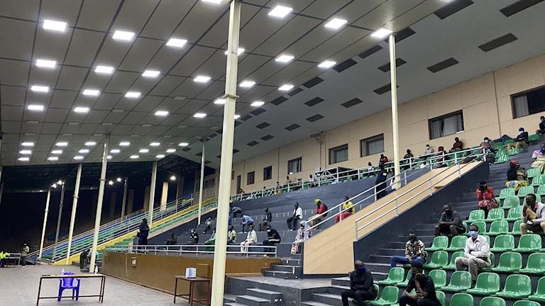 Läktare på en idrottsarena. Där sitter många människor och lyssnar på föreläsning om corona.