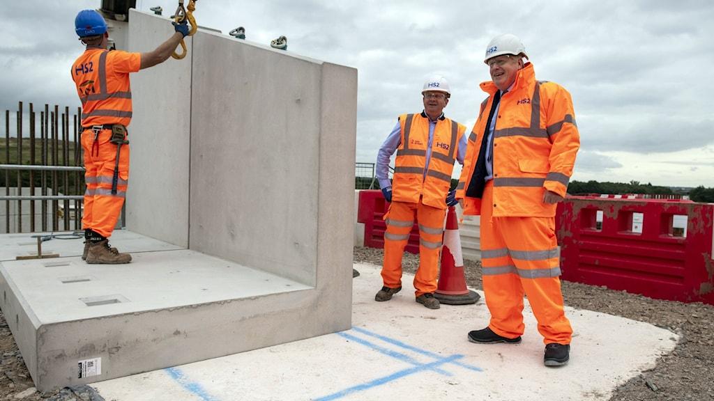 Män i orangefärgade kläder hanterar stora betongblock
