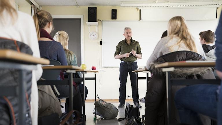 Lärare undervisar barn på gymnasiet.