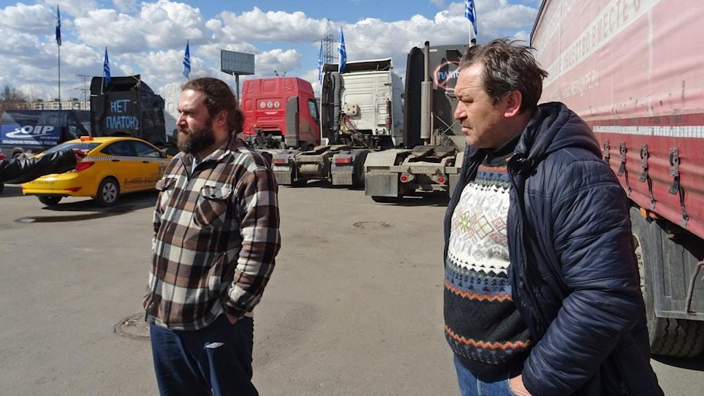 Två män står framför lastbilar
