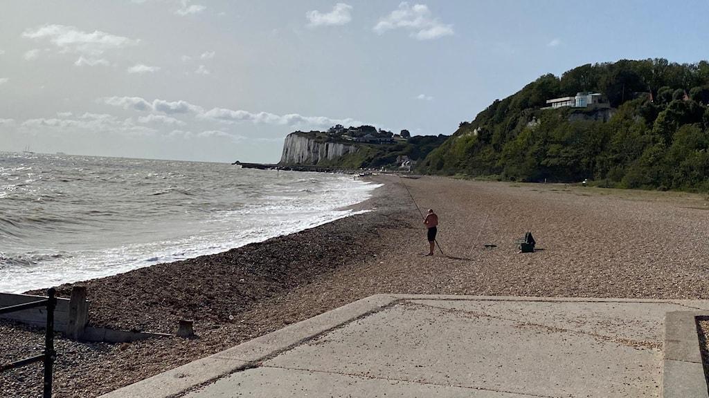 Strand med fiskare.