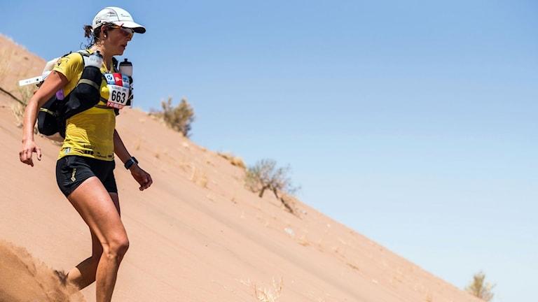 kvinna springer ett lopp i öken, ryggsäck, shorts och keps