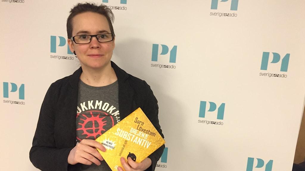 Sara Lövestam håller en bok i handen.