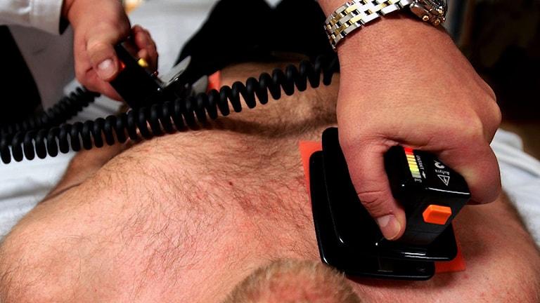 Läkare håller hjärtstartare mot bröstet på patient. Foto: Björn Larsson Ask/Scanpix.