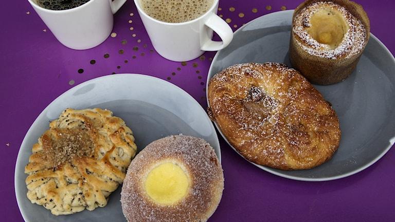 Flera bakverk och två koppar kaffe står på ett lila cafébord.