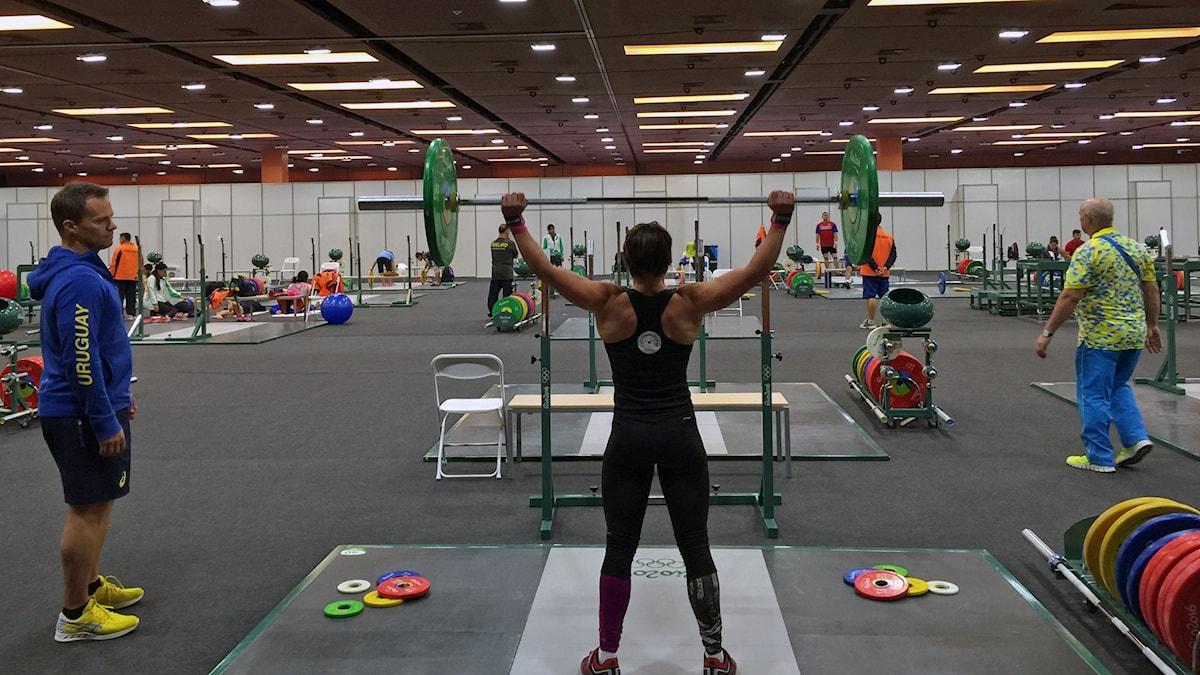 Sofia Enocsson Rito lyfter vikter i träningshallen i Rio. Tränaren Gunnar Lögdahl ger instruktioner.