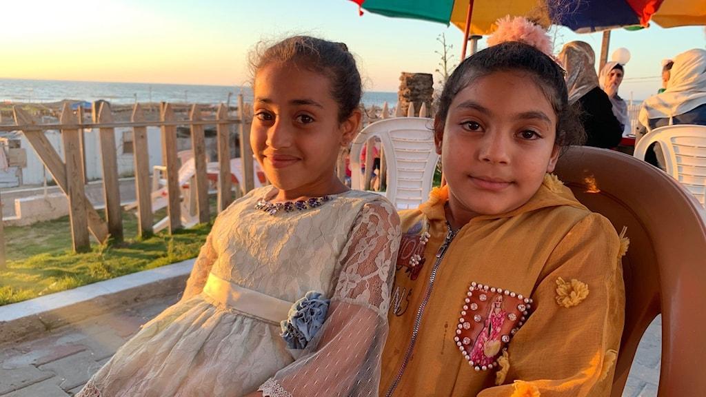 8-åriga May i vit spetsblus och hennes kompis Shahid.