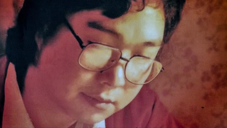 Bild på man med svart hår och glasögon som tittar nedåt. Orangeröd ton i bilden.