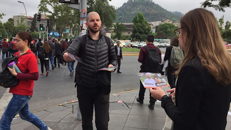 En man delar ut flygblad på en gata.