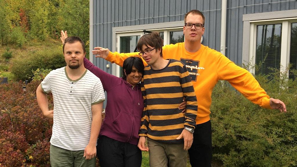 Fyra glada personer står utanför ett hus och spexar.