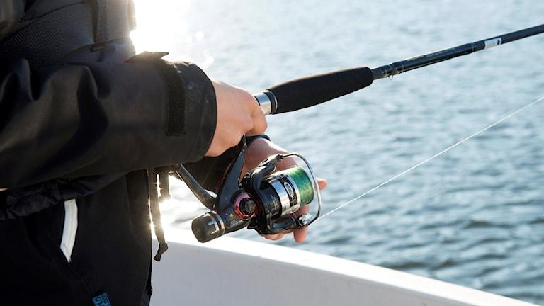 Fiskespö som hålls av en man som står i en båt
