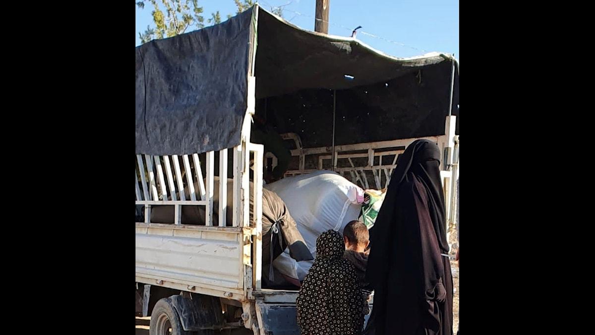 En pickup och bakom den s tår en kvinna och håller ett par barn i handen.