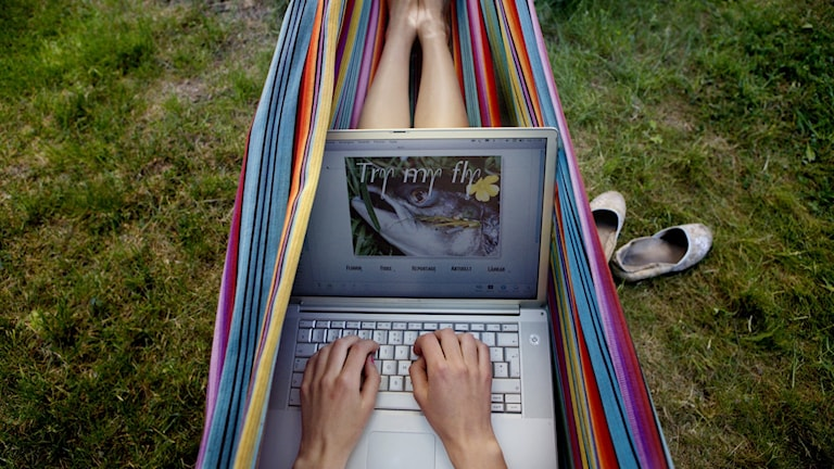 En kvinna ligger i en hängmatta och surfar med sin bärbara dator