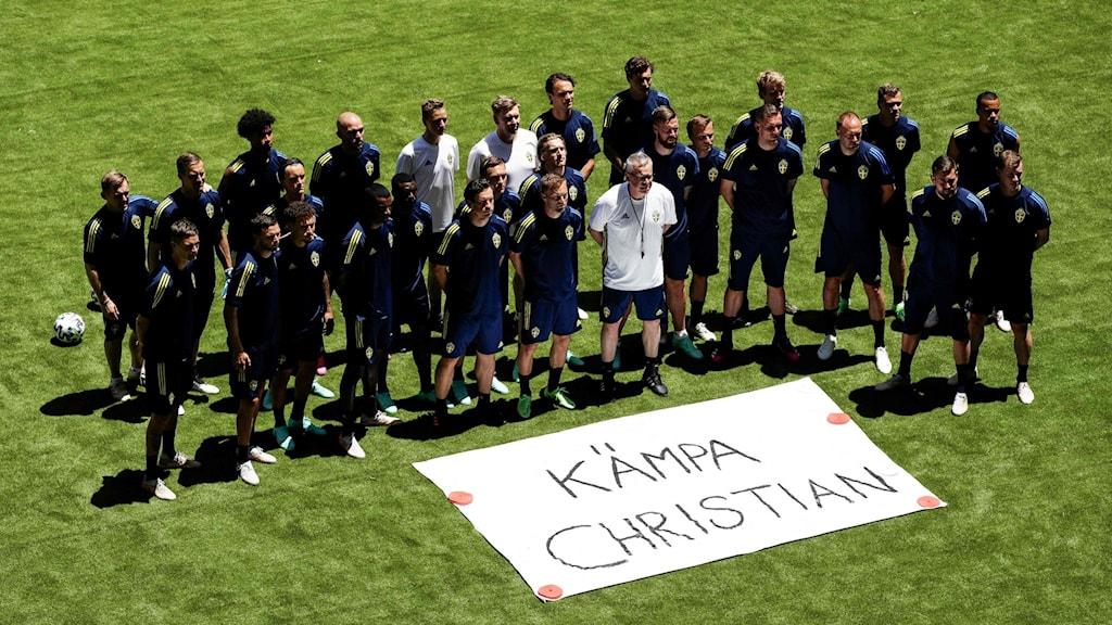 Fotbollsspelare framför en skylt i gräset där det står Kämpa Christian.