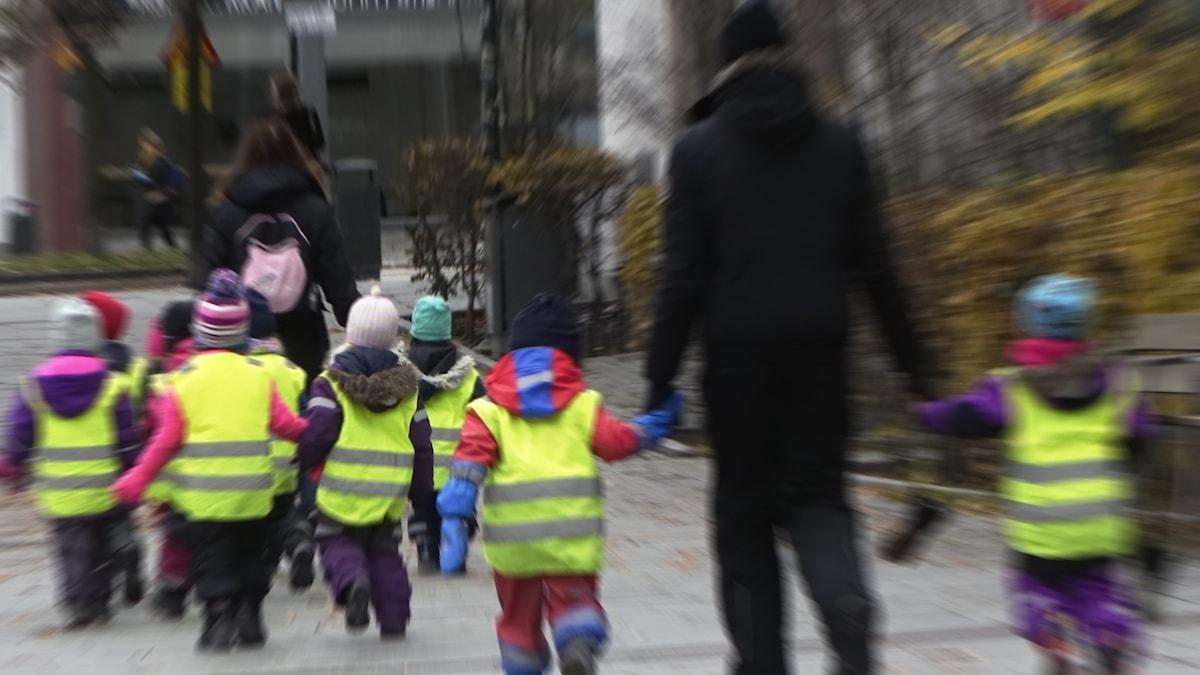 Förskolebarn och personal på promenad.