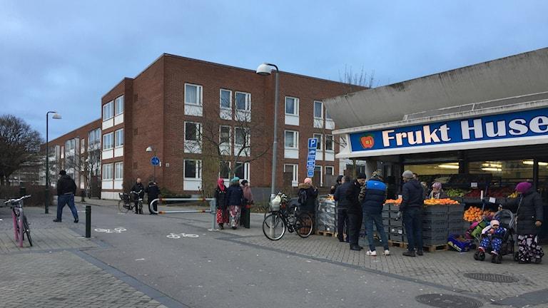Bilden visar Örtagårdstorget på Rosengård i Malmö. I förgrunden en fruktaffär med kunder, i bakgrunden syns trevåningshus i rött tegel. Foto: Anna Bubenko/Sveriges Radio.