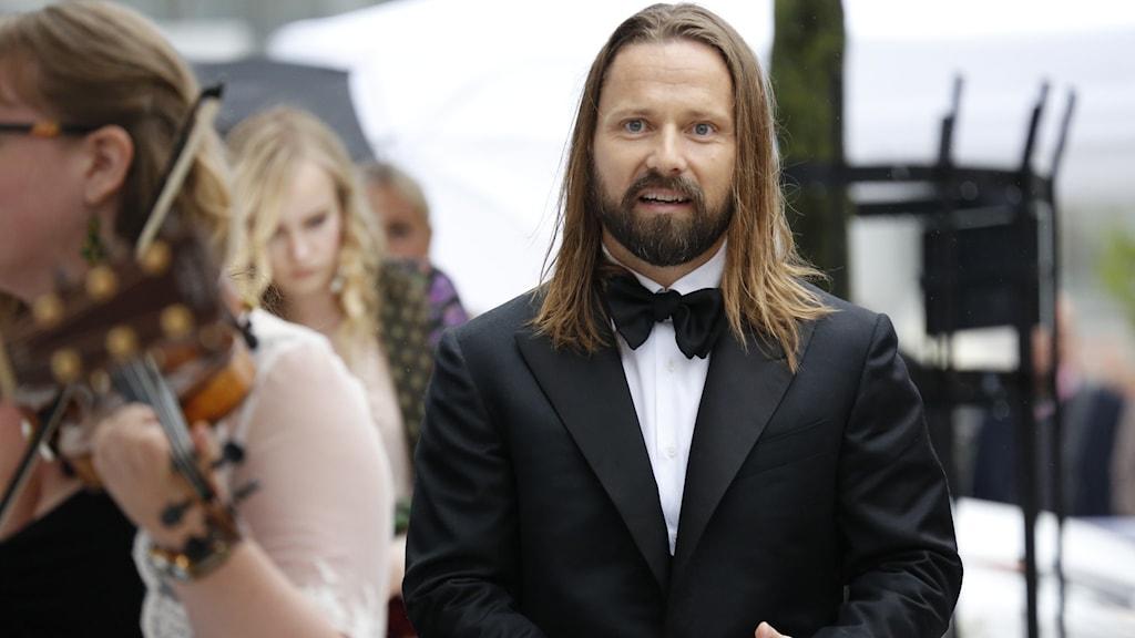 En man red långt brunt hår i svart kostym.