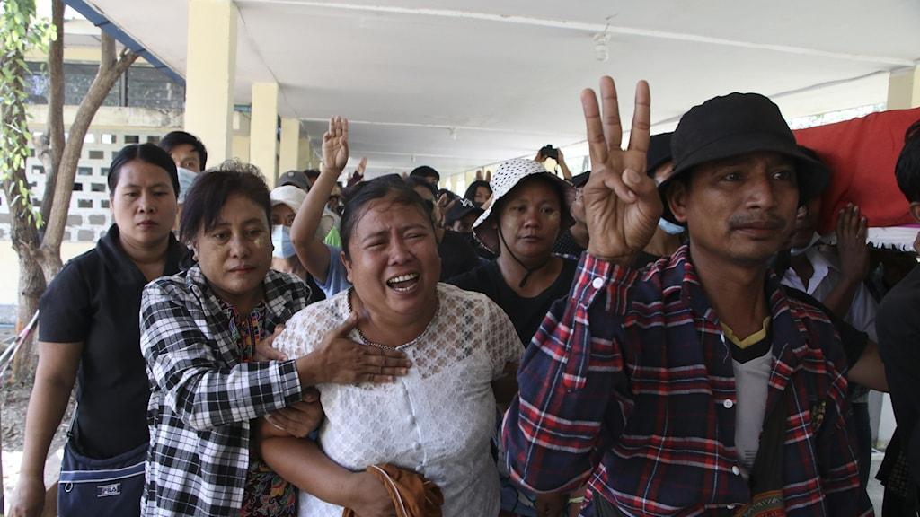 Bild på sörjande som visar tre-finger-tecknet, under minnesstund för person som dödats i protesten.