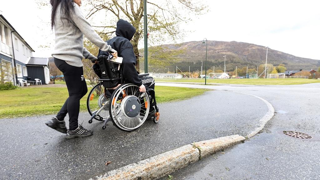 Man i rullstol med personlig assistent.