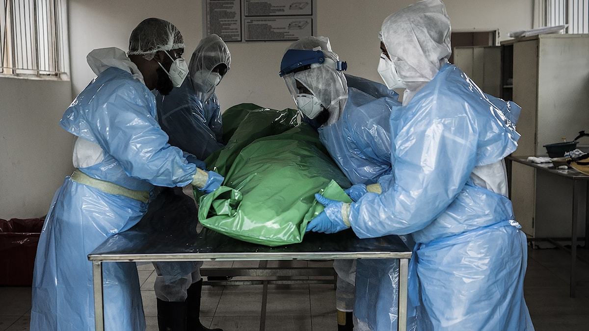 """Members of the Saaberie Chishty Burial Society prepare the body of a person who died from COVID-19 at the Avalon Cemetery in Lenasia, Johannesburg Saturday Dec. 26, 2020. South Africa's health minister has announced an """"alarming rate of spread"""" in the country, with more than 14,000 new confirmed coronavirus cases and more than 400 deaths reported Wednesday. It was the largest single-day increase in cases. (AP Photo/Shiraaz Mohamed).  XDF101"""