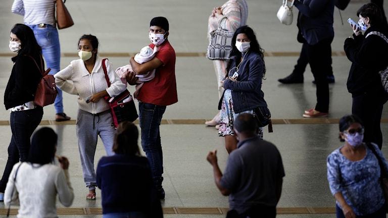 personer med munskydd p en busstation i Brasilien.