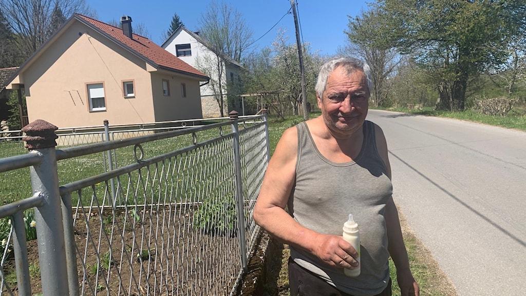 Man i grått linne står framför ett staket med en nappflaska i handen.