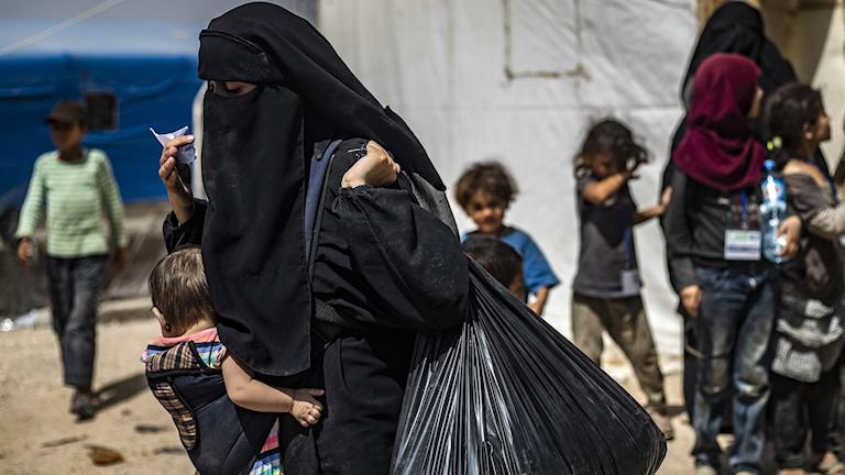 Mamma i Al-Hol-lägret bär sitt barn.