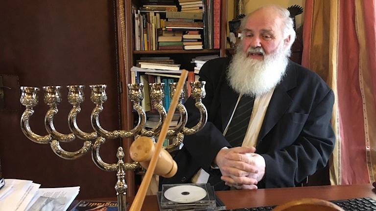 Ungerska prästen Gábor Iványi sitter vid bakom ett bord med en stor ljusstake på, han har långt vitt skägg.
