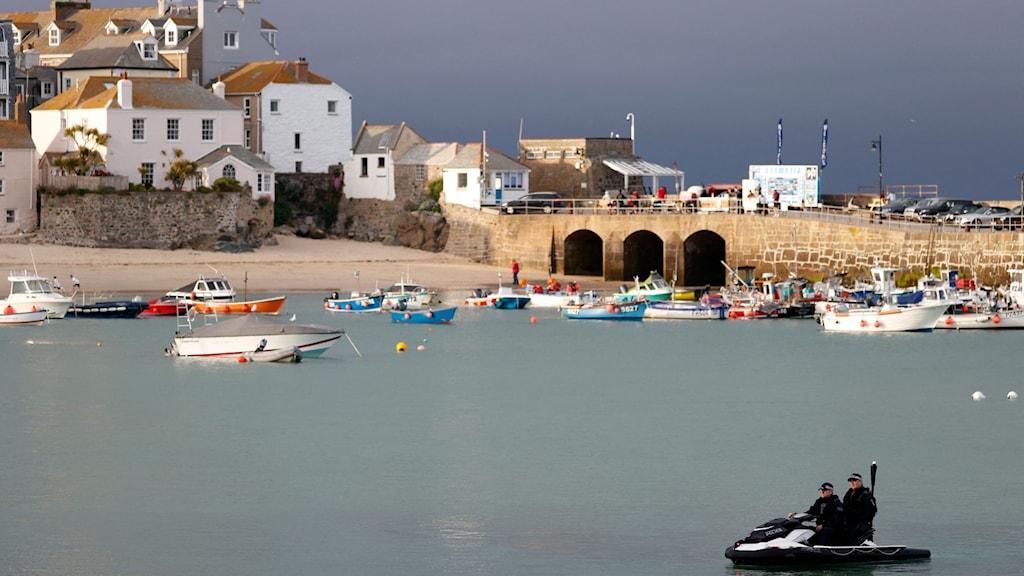 Två poliser på liten vattenskoter patrullerar kusten i Cornwall