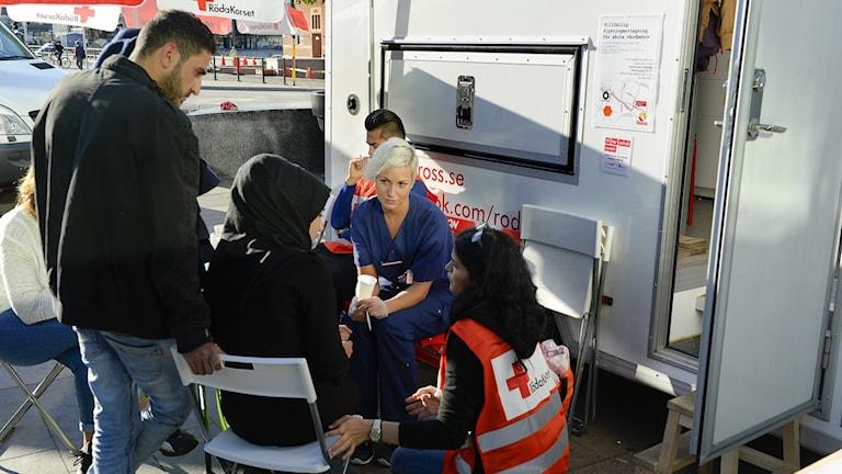 Personal från Röda Korset talar med flyktingar.
