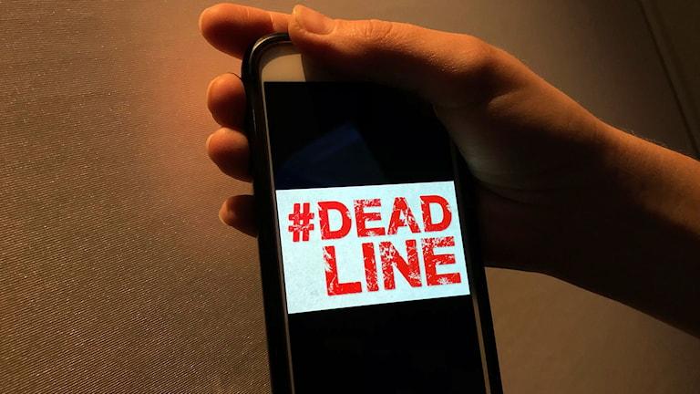 bild på att en kvinna håller en mobiltelefon och loggan #deadline är på skärmen
