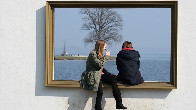 Sevärdhet i Schwerin: Två tjejer tittar ut genom fönster som ser ut som en tavelram.