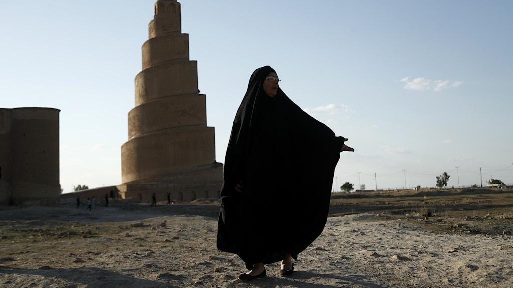Kvinna i fotsid svart dräkt framför spiralminareten i Samarra.