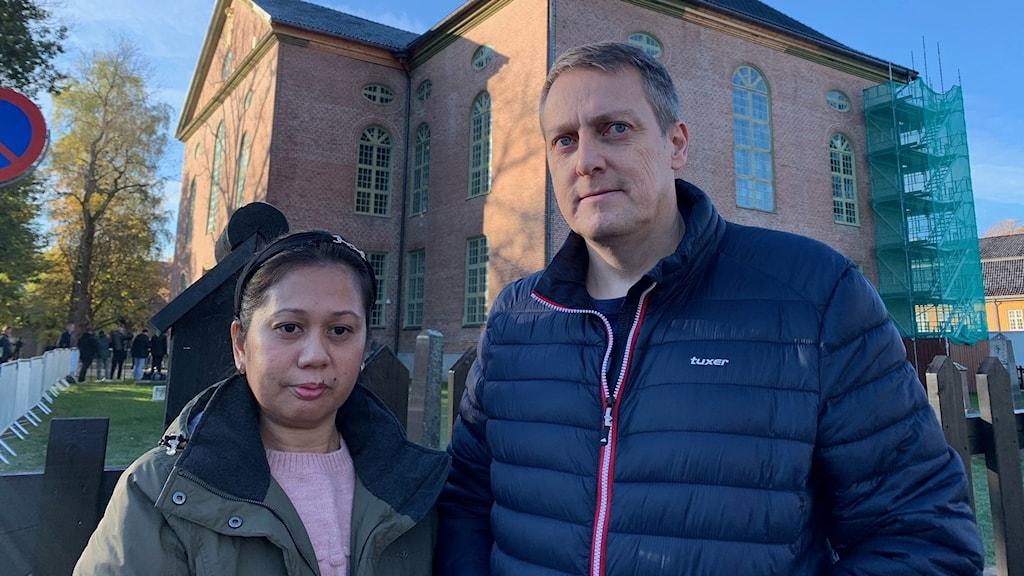 En kvinna och en man framför en kyrka.