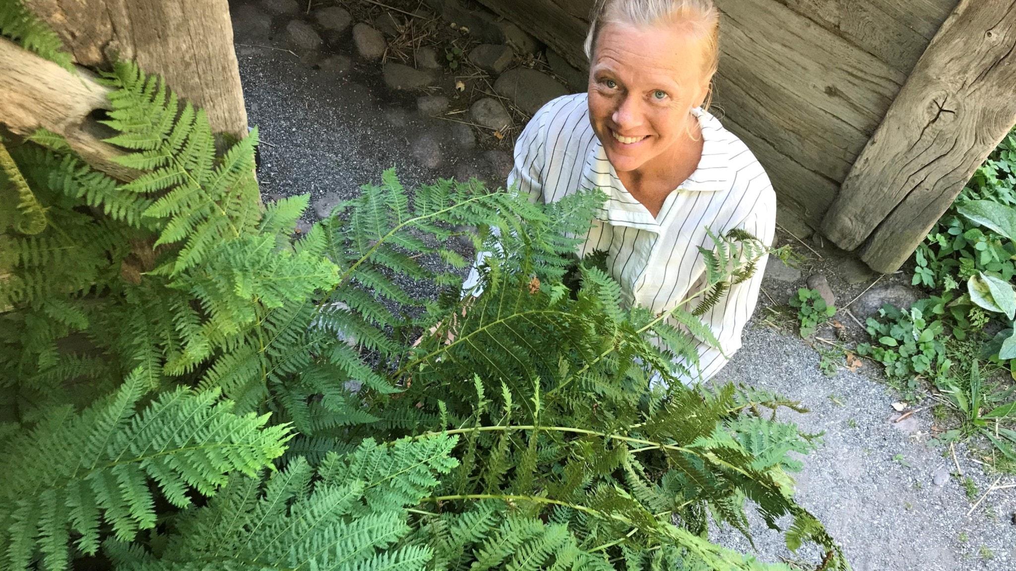 Tina Wedterlund hukar bakom en grön ormbunke