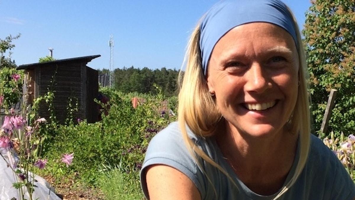 Tina Westerlund i närbild, skrattar, blont långt hår, blått hårband, blått linne, grönt koloniområde i bakgrunden.