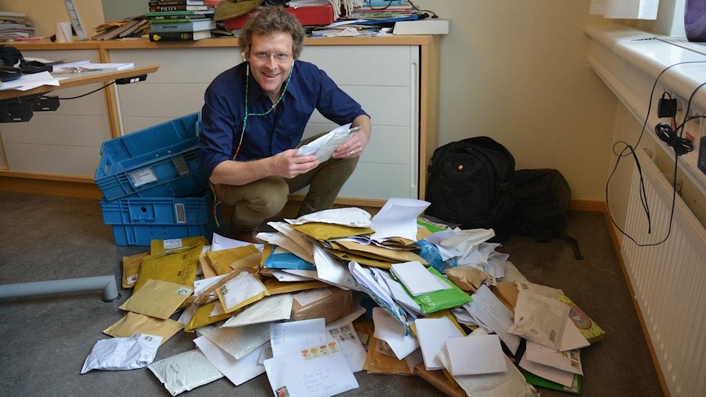 Gustaf Klarin på huk bakom en hög med 150 brev och paket med aska som lyssnare skickat in till Odla med P1.