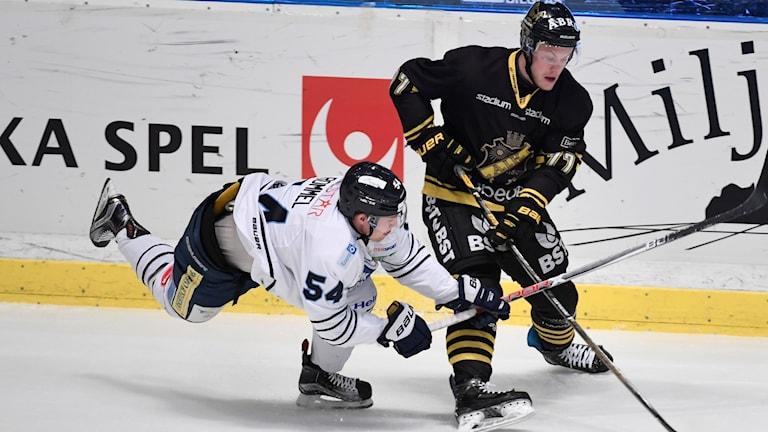 Karlskogas Henrik Rommell försöker stoppa Jacob Spångberg under en ishockeymatch.