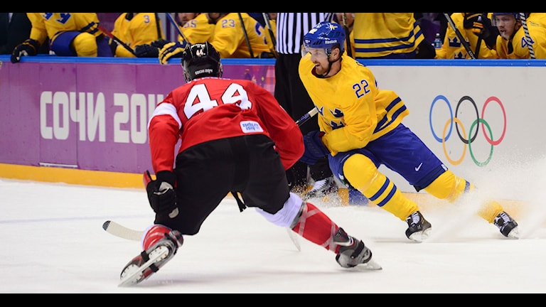 Canada's Marc-Edouard Vlasic (L) vies with Sweden's Daniel Sedin during the Men's ice hockey final Sweden vs Canada at the Bolshoy Ice Dome during the Sochi Winter Olympics on February 23, 2014. AFP PHOTO / JOHN MACDOUGALL