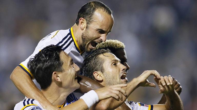 Stefan Ishizaki, Landon Donovan och Marcelo Sarvas firar. Foto: AP/TT