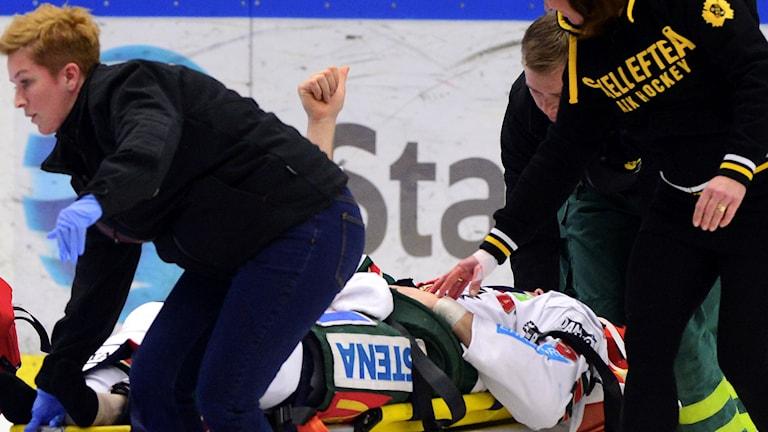 Christian Bäckman ger tummen upp från båren. Foto: Robert Granström/TT