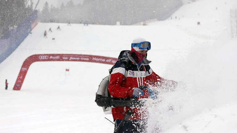 A course crew volunteer clears snow from the finish area for the men's super-G race at the alpine skiing world championships, Wednesday, Feb. 4, 2015, in Beaver Creek, Colo. The was canceled because of too much snow. AP Photo/Brennan Linsley